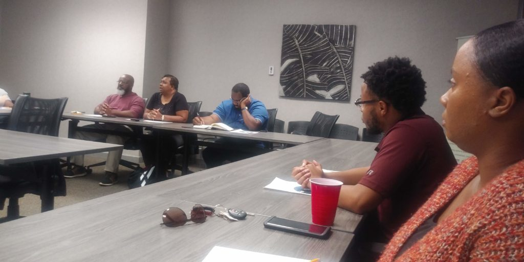 October Chapter Meeting at Huntsville Hub, chapter members sitting in a conference room having a discussion.